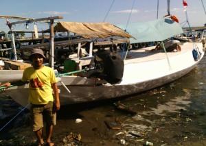 Muhammad Ridwan Alimuddin berpose di belakang Perahu Pustaka saat berlabuh di Makassar